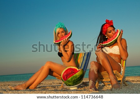 Young stylish ladies at sea with watermelon and a drink relaxing on deck chair - stock photo