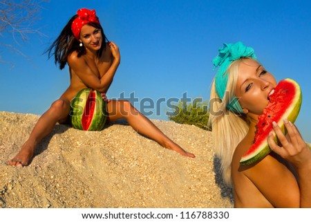 Young stylish ladies with watermelon on sand against blue sky - stock photo