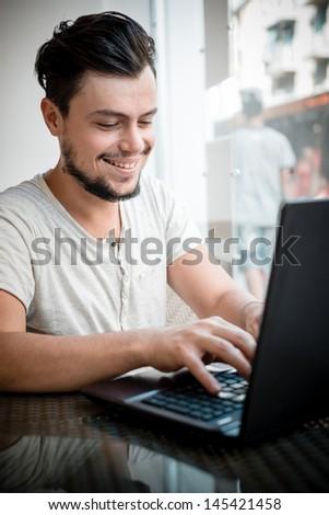 young stylish man at the bar using notebook