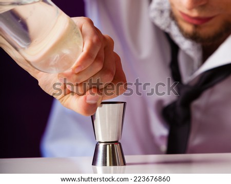Young stylish man bartender preparing serving alcohol cocktail drink, pouring vodka filling a jigger - stock photo