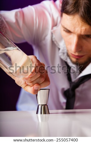 Young stylish man bartender preparing serving alcohol cocktail drink, pouring vodka filling a jigger
