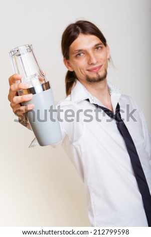 Young stylish man bartender with shaker making alcohol cocktail drink studio shot on gray