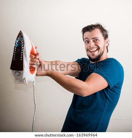 young stylish man housewife ironing at home - stock photo