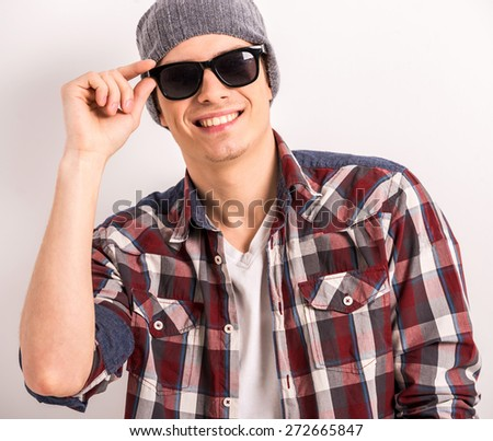 Young stylish man in black glasses and casual clothes over gray background.
