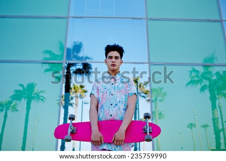 Young stylish man in bright summer clothes standing with pink long-board on beautiful glass background with reflected palm trees - stock photo