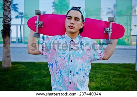 Young stylish man in bright summer clothes standing with pink long-board on beautiful glass background with reflected palm trees, cool teenager holding his long board looking away - stock photo