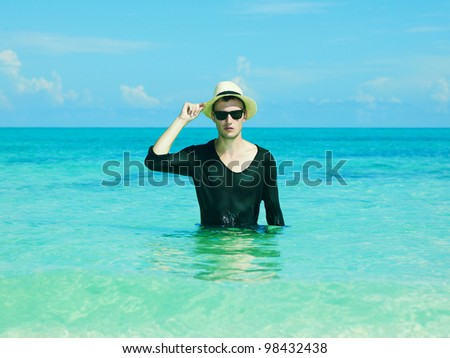 Young stylish man in the hat jumps on the sea - stock photo