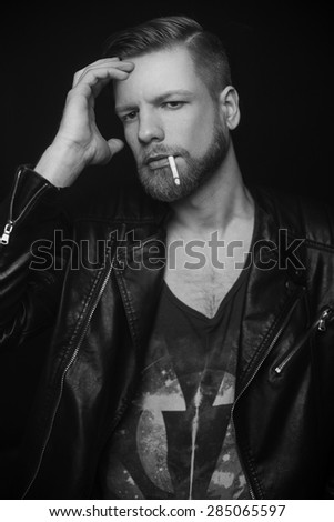 Young stylish man is smoking a cigarette. Studio portrait over black background