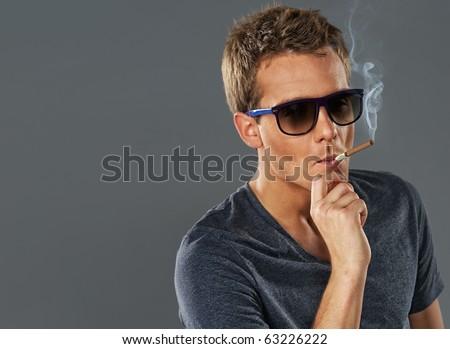 Young stylish man smoking a cigarette - stock photo