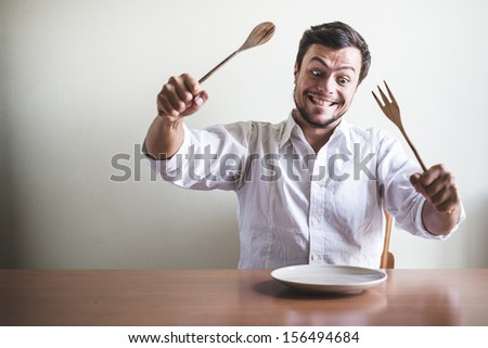 young stylish man with white shirt eating in mealtimes behind a table - stock photo