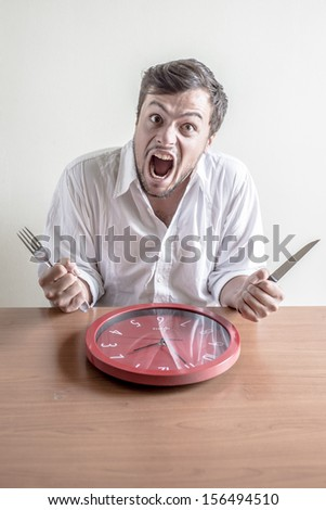 young stylish man with white shirt eating red clock behind a table - stock photo