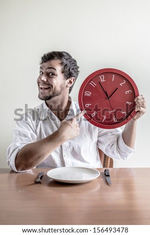 young stylish man with white shirt holding red clock behind a table - stock photo