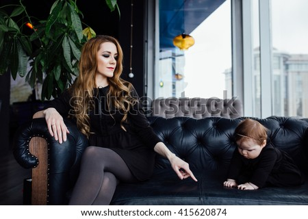 Young stylish  mother with her adorable baby girl in  hipster cafe. A fashion mom and toddler. Sitting on a leather couch. Overbearing mother - stock photo