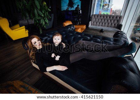 Young stylish  mother with her adorable baby girl in  hipster cafe. A fashion mom and toddler. Mother lying on a leather couch,  daughter is sitting on her stomach. - stock photo