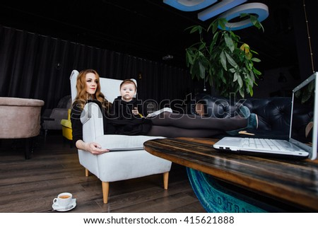 Young stylish  mother with her adorable baby girl in  hipster cafe. A working fashion mom and toddler. Hugging her daughter sitting in a chair in front of computer. successful mom shoes on the desk - stock photo
