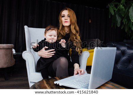 Young stylish  mother with her adorable baby girl in  hipster cafe. fashion mom and toddler. Hugging her daughter sitting in a chair in front of computer and working. - stock photo