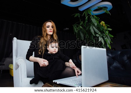 Young stylish  mother with her adorable baby girl in  hipster cafe. fashion mom and toddler. Hugging her daughter sitting in a chair in front of computer and working. playful daughter prevents to work - stock photo