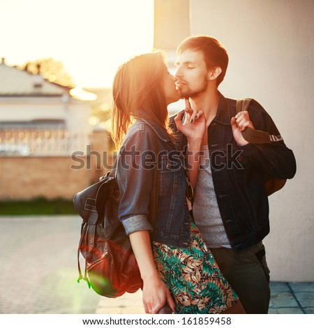 Young stylish pretty couple in love posing outdoor in the city while kissing and having fun in summer at sunset - stock photo