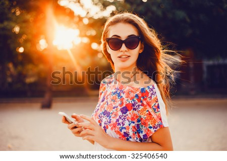 young stylish pretty woman, hands holding a phone, denim shirt and jeans, sunset background, hat, backpack, sunny day, good weather, tropical mood, vacation Spain travel, detail, cool accessories - stock photo