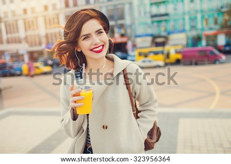 young stylish pretty woman with juice posing in the city streets. vacation europe - stock photo
