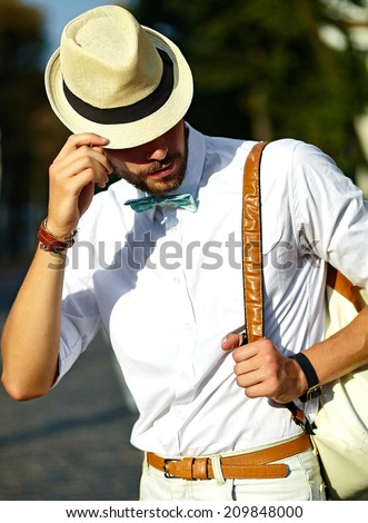 Young stylish sexy handsome model man tourist in casual cloth lifestyle in the street in hat with bag - stock photo