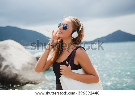 young stylish sexy hipster woman with a shopping bag on vacation, aviator sunglasses, headphones, listening to music, happy, enjoying sun, tropical island blue lagoon landscape - stock photo