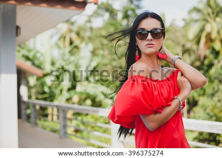 young stylish sexy woman in red summer dress standing on terrace in tropical hotel, palm trees background, long black hair, sunglasses, ethnic earrings, sunglasses,  smiling - stock photo
