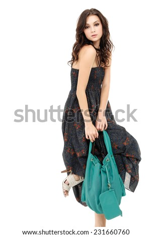 young stylish slim woman with handbag posing in studio  - stock photo