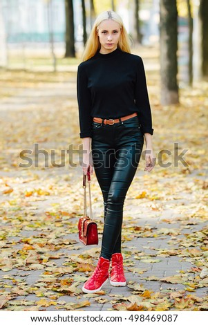 Young stylish sporty blond beautiful teen girl in black posing at park on a warm golden fall day against blurred yellow foliage background. Teen urban city outfit. Film saturated color.