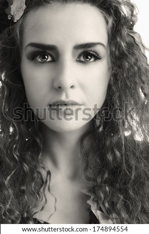 Young stylish teen portrait with artistic make-up and autumn leafs in her hair. Black and white version. - stock photo