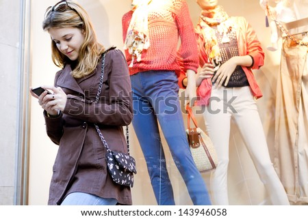Young stylish teenager woman using a smartphone device while visiting the city, leaning on a fashion store shop window while shopping for clothes. - stock photo