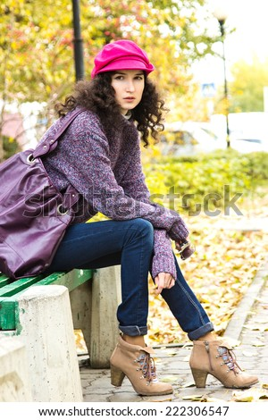 Young stylish woman dressed in oversized knitted sweater, skinny jeans, peaked cap and heels with big bag sitting on bench in city park. Fashion beautiful girl