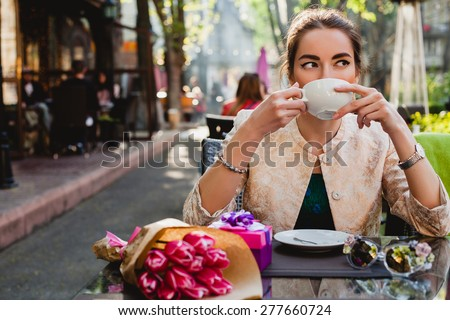 young stylish woman, fashion sunglasses, sitting in cafe, holding drinking cup cappuccino, enjoying, tulips, happy birthday party, city street, boho outfit, europe vacation, romantic dinner, sunny - stock photo