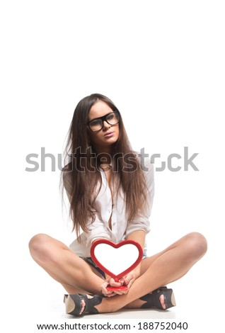 Young stylish woman holding empty heart shaped picture frame. - stock photo