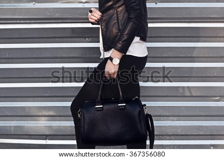 Young stylish woman in black trendy outfit with big bag in hand street look  - stock photo
