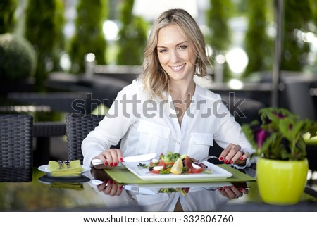 young stylish woman sitting in cafe,  enjoying healthy food, city street, boho outfit, europe vacation, fashion