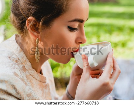 young stylish woman, sitting in cafe, holding drinking cup cappuccino, boho outfit, europe vacation, romantic dinner, gift, close up, detail, face