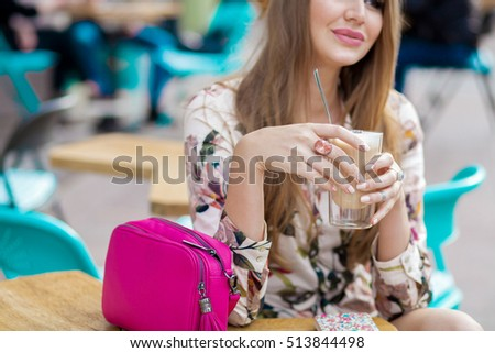 young stylish woman sitting in cafe, spring summer trend outfit, drinking cup of cappuccino, bohemian style, close-up details, pink bag, note