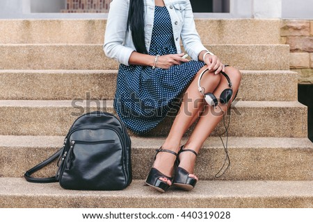 young stylish woman sitting on stairs, holding headphones in hands, backpack, long legs, high heel shoes, tanned skin, close-up details, accessories - stock photo