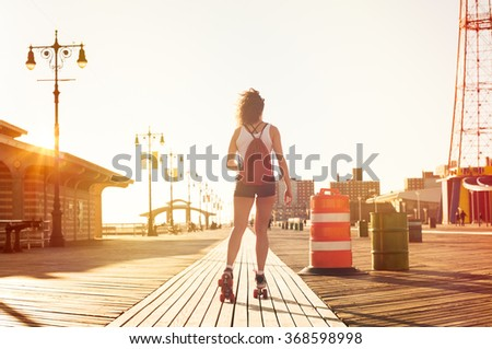 Young stylish woman skating on footpath during sunset. Young sporty girl rollerblading on skates. Young woman in casual skating on the footpath during summer sunset in a urban landscape. - stock photo