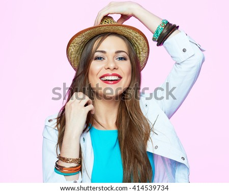 Young stylish woman smiling on pink background. Female model with hat and long hair. - stock photo
