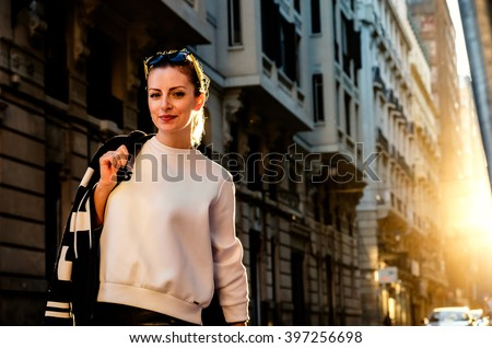 Young stylish woman stands at the road on the street at sunset. Fashion