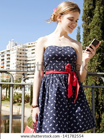 Young stylish woman using a smartphone while standing on a city bridge overlooking a river and holding shopping paper bags during a sunny day with a blue sky. - stock photo