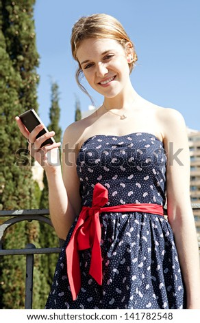 Young stylish woman using a smartphone while standing on a city bridge, smiling at the camera during a sunny day with a blue sky. - stock photo