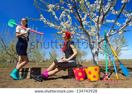 Young stylish woman using laptops sitting on wooden box