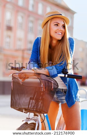 Young stylish woman with a bicycle in a city street - stock photo