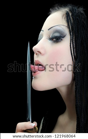 young stylish woman with dreadlocks, licking a dagger isolated on black - stock photo
