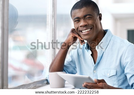 young successful black african man with morning coffee and tablet computer checking on news of investments - stock photo