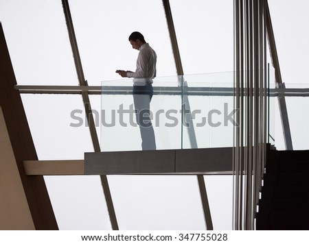 young successful business man in penthouse working on tbalet,  modern bright duplex office apartment interior  with staircase and big windows