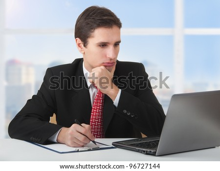 young successful business man working behind the notebook, sitting at a desk against the window